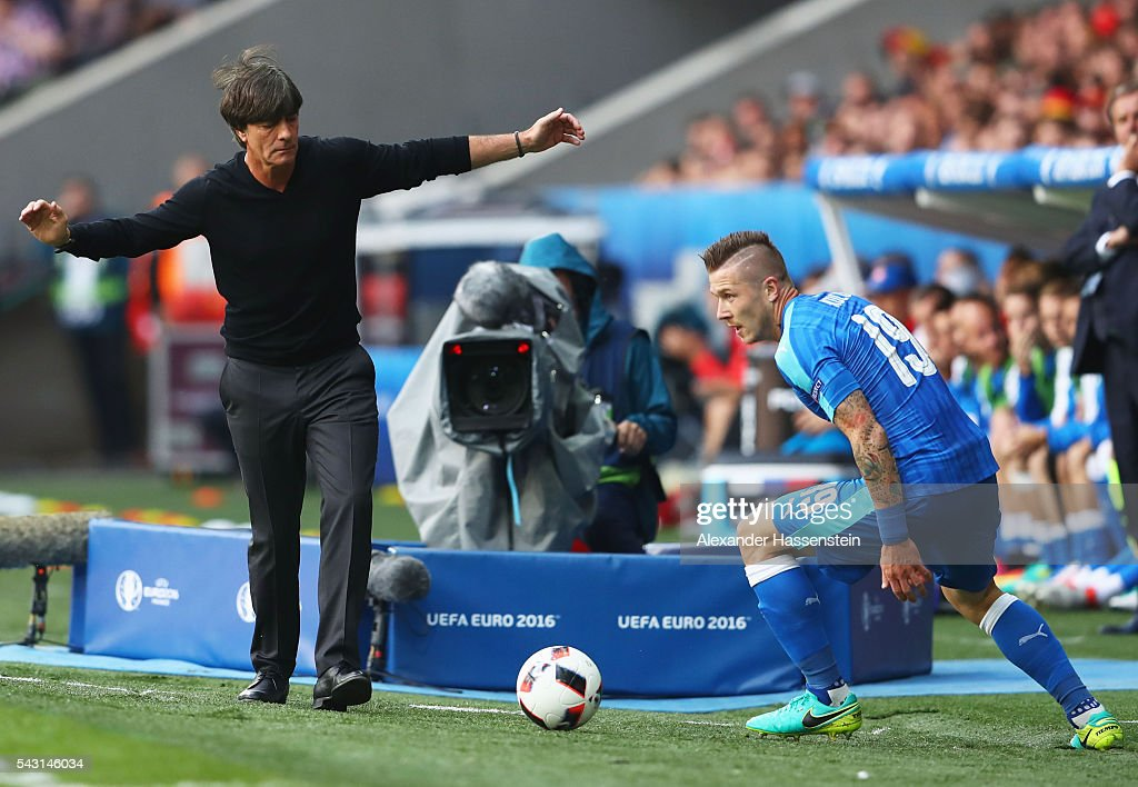 Juraj Kucka of Slovakia picks up the ball outside the pitch while Joachim Loew head coach of Germany reacts during the UEFA EURO 2016 round of 16 match between Germany and Slovakia at Stade Pierre-Mauroy on June 26, 2016 in Lille, France.