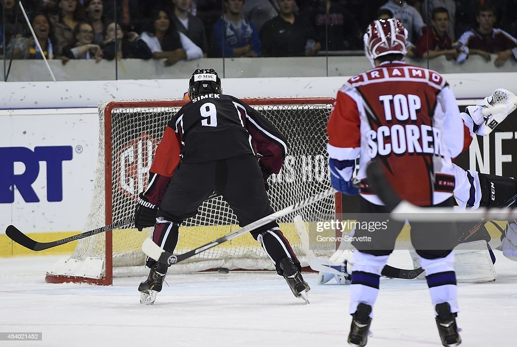 Juraj Simek of Geneve-Servette shots the 4th goal against Brock McBride and goalie Jean-Philippe Lamoureux of Villach SV during the Champions Hockey League group stage game between Geneve-Servette and Villach SV on August 23, 2014 in Geneva, Switzerland.