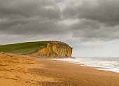 Cold sea surf on beach by Jurassic Coast cliffs and headland at West Bay in Dorset used as the location for the Broadchurch TV series