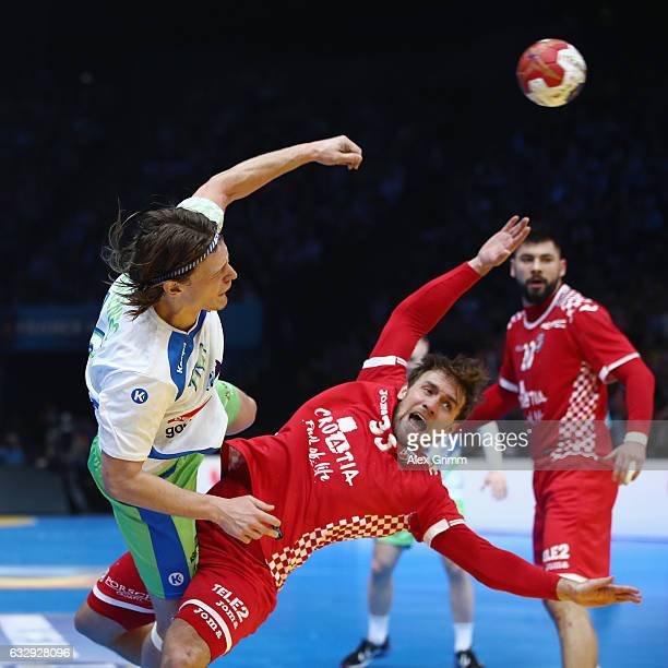 Jure Dolenec of Slovenia is challenged by Luka Cindric of Croatia during the 25th IHF Men's World Championship 2017 Bronze Medal Game between...