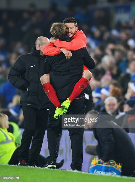 Jurgen Klopp manager of Liverpool and Adam Lallana of Liverpool celebrate victory after the Premier League match between Everton and Liverpool at...