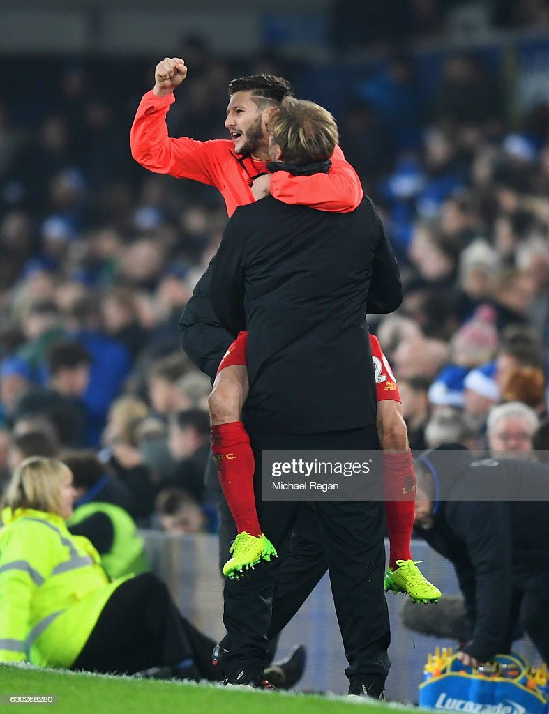 Jurgen Klopp manager of Liverpool and Adam Lallana of Liverpool celebrate victory after the Premier League match between Everton and Liverpool at Goodison Park on December 19, 2016 in Liverpool, England.