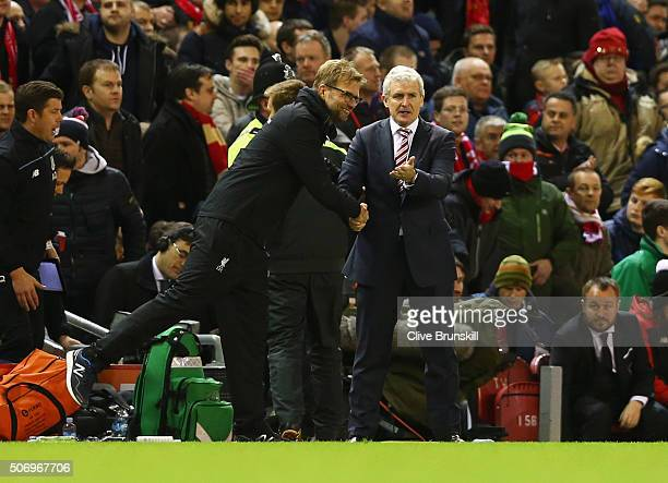 Jurgen Klopp manager of Liverpool and Mark Hughes manager of Stoke City shake hands during the Capital One Cup semi final second leg match between...