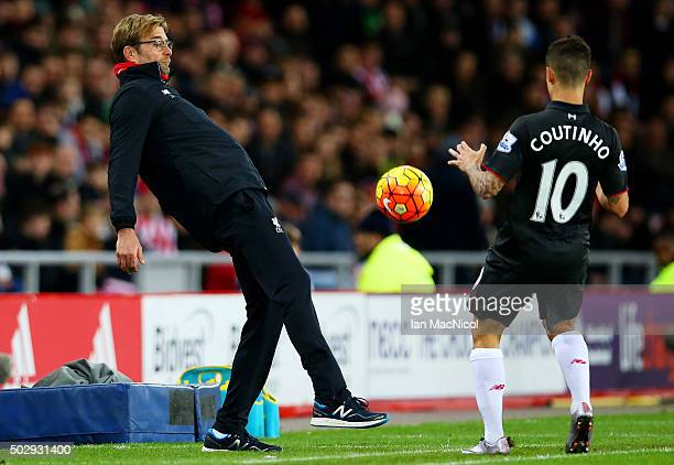 Jurgen Klopp manager of Liverpool attempts to control the ball for Philippe Coutinho of Liverpool during the Barclays Premier League match between...
