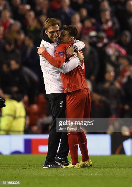 Jurgen Klopp manager of Liverpool hugs Adam Lallana of Liverpool at the end of the UEFA Europa League Round of 16 first leg match between Liverpool...