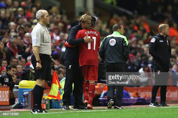 Jurgen Klopp manager of Liverpool hugs Roberto Firmino of Liverpool as he is substituted during the Capital One Cup Fourth Round match between...