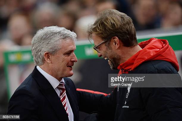 Jurgen Klopp Manager of Liverpool is greeted by Mark Hughes the Manager of Stoke City during the Capital One Cup semi final first leg match between...