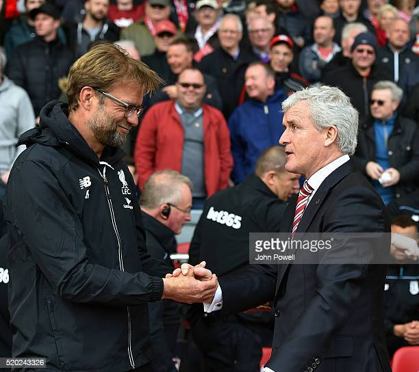 Jurgen Klopp manager of Liverpool shakes hads with Mark Hughes manager of Stoke City before the Barclays Premier League match between Liverpool and...