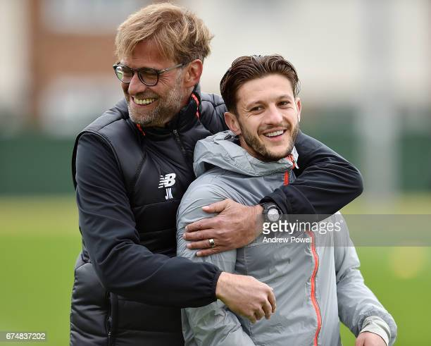 Jurgen Klopp manager of Liverpool with Adam Lallana during a training session at Melwood Training Ground on April 29 2017 in Liverpool England
