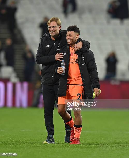 Jurgen Klopp Manager of Liverpool with Alex OxladeChamberlain at the end of the Premier League match between West Ham United and Liverpool at London...