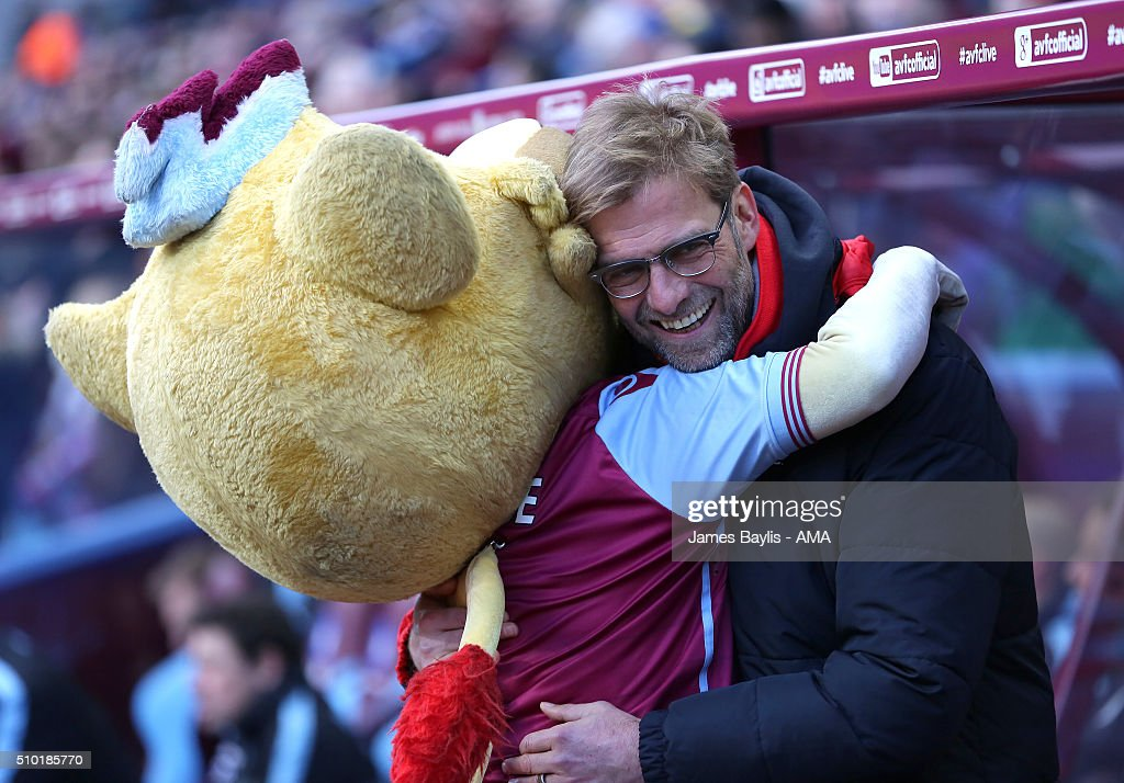 Jurgen Klopp the head coach / manager of Liverpool is hugged by the Aston Villa mascot during the Barclays Premier League match between Aston Villa and Liverpool at Villa Park on February 14, 2016 in Birmingham, England.