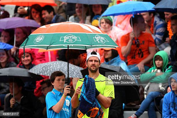 Jurgen Melzer of Austria waits for play to start as he shelters from the rain under an unbrealla during his men's singles match against David Goffin...