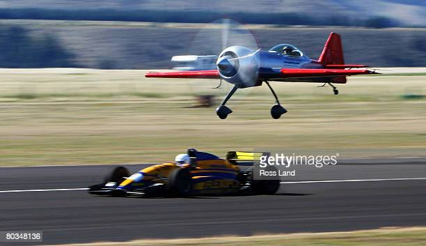 Jurgis Kairys of the Airbandits in his Sukhoi races Jihn Crawford in his F 3000t racecar during the Warbirds Over Wanaka airshow on April 23 2008 in...