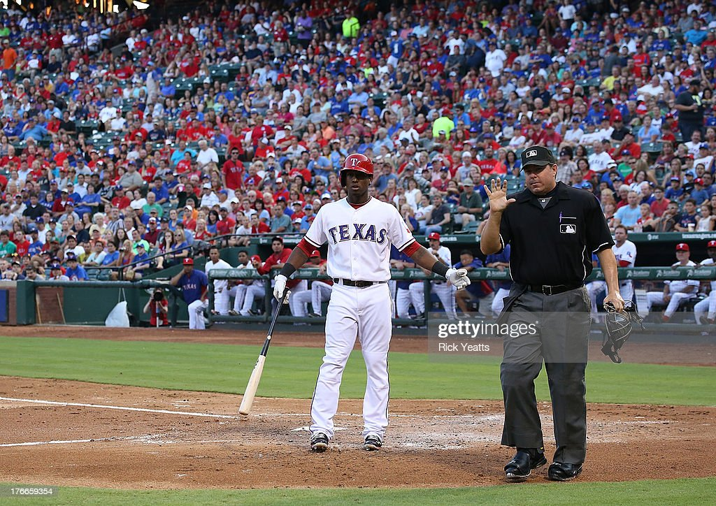 Jurickson Profar #13 of the Texas Rangers reacts to a third strike call as home plate umpire Doug Eddings #88 monition to (not pictured) Humberto Quintero #35 of the Seattle Mariners for the ball for bat marks at Rangers Ballpark in Arlington on August 16, 2013 in Arlington, Texas.