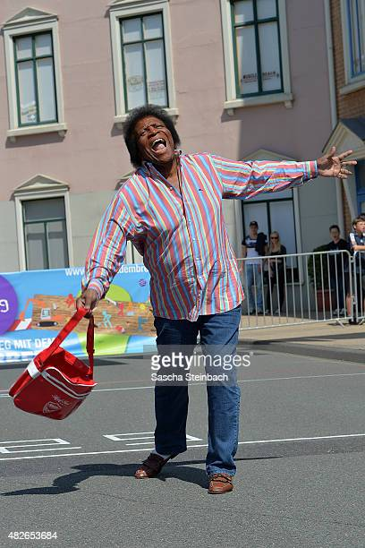 Jury member Roberto Blanco launches a handbag prior to the 4th annual World Handbag Throwing Championships at Movie Park Germany on August 1 2015 in...