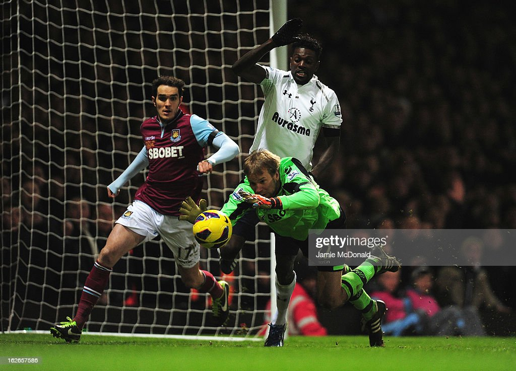 Jussi Jaaskelainen of West Ham United dives on the ball challenged by Emmanuel Adebayor of Tottenham Hotspur as Joey O'Brien of West Ham United looks on during the Barclays Premier League match between West Ham United and Tottenham Hotspur at the Boleyn Ground on February 25, 2013 in London, England.