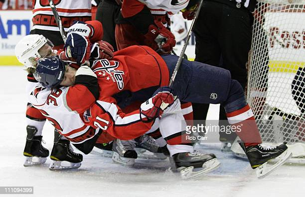 Jussi Jokinen of the Carolina Hurricanes pulls Brooks Laich of the Washington Capitals to the ice during the first period at the Verizon Center on...