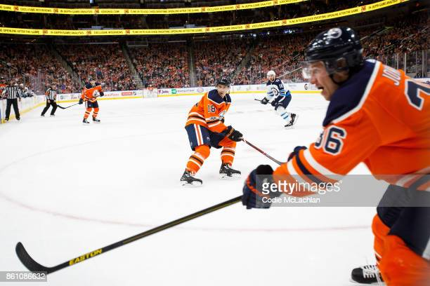 Jussi Jokinen of the Edmonton Oilers makes a pass as teammate Ryan Strome looks on under pressure from Bryan Little of the Winnipeg Jets at Rogers...