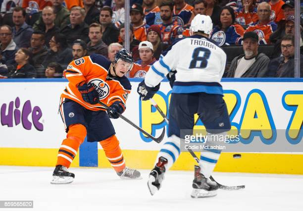 Jussi Jokinen of the Edmonton Oilers passes the puck against Jacob Trouba of the Winnipeg Jets at Rogers Place on October 9 2017 in Edmonton Canada