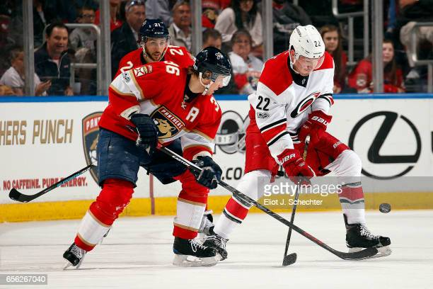 Jussi Jokinen of the Florida Panthers crosses sticks with Brett Pesce of the Carolina Hurricanes during second period action at the BBT Center on...