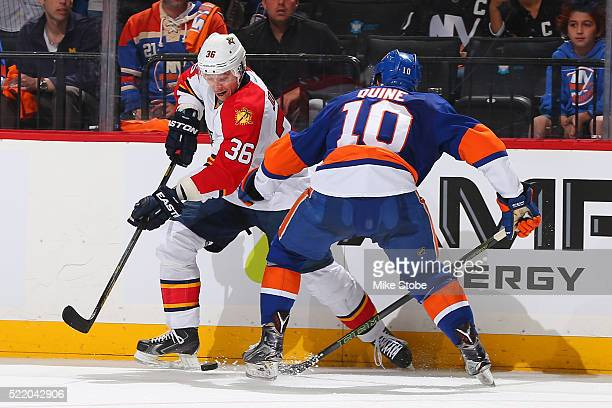 Jussi Jokinen of the Florida Panthers plays the puck in front of Alan Quine of the New York Islanders in Game Three of the Eastern Conference...