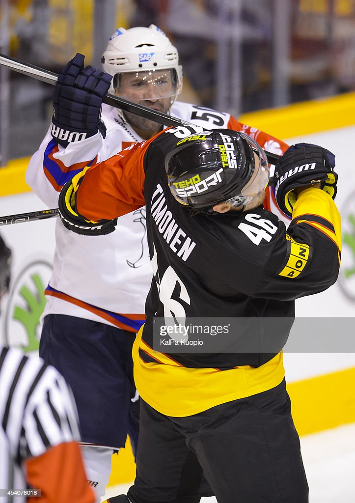 Jussi Timonen #46 of KalPa Kuopio is checked during the Champions Hockey League group stage game between KalPa Kuopio and Adler Mannheim on August 24, 2014 in in Kuopio, Finland.