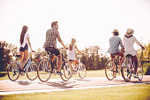 Group of young cheerful people riding bicycles along a road