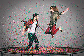Mid-air shot of beautiful young cheerful couple jumping on trampoline together with confetti all around them