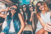 Four beautiful young cheerful women looking happy and playful while sitting in car