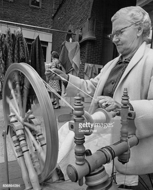 Just Going for a Little Spin Mrs Alvin Jacobson of 717 Cove Way shows how a spinning wheel is operated Scene is Larimer Square where members of the...