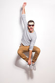 Excited young man jumping in front of the white wall and keeping mouth open