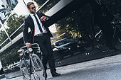 Full length of handsome young man in full suit pulling his bicycle and checking the time while walking outdoors