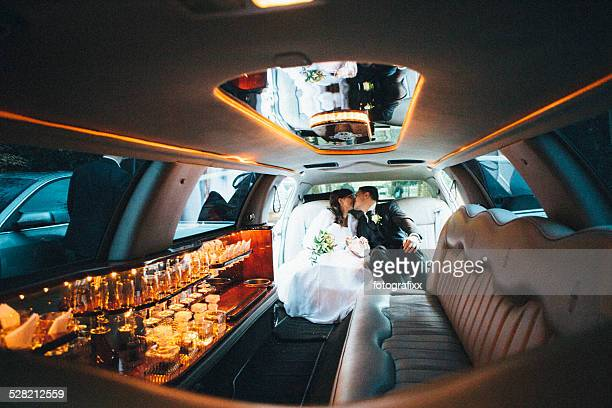 just married: Bride and groom sitting in a stretch limousine