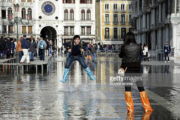 A just married Canadian couple on a honey moon trip in Venice plays with the water in front of the Doge's Palace on November 4 2013 in Venice Saint...