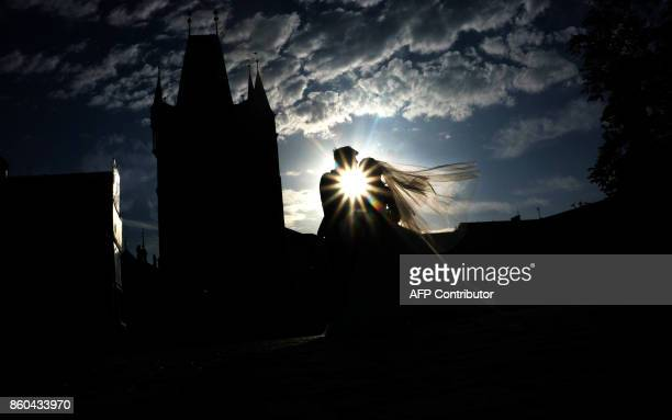 TOPSHOT A just married couple from Asia pose for their photographer on the Charles Bridge on the early morning of October 12 2017 in Prague / AFP...