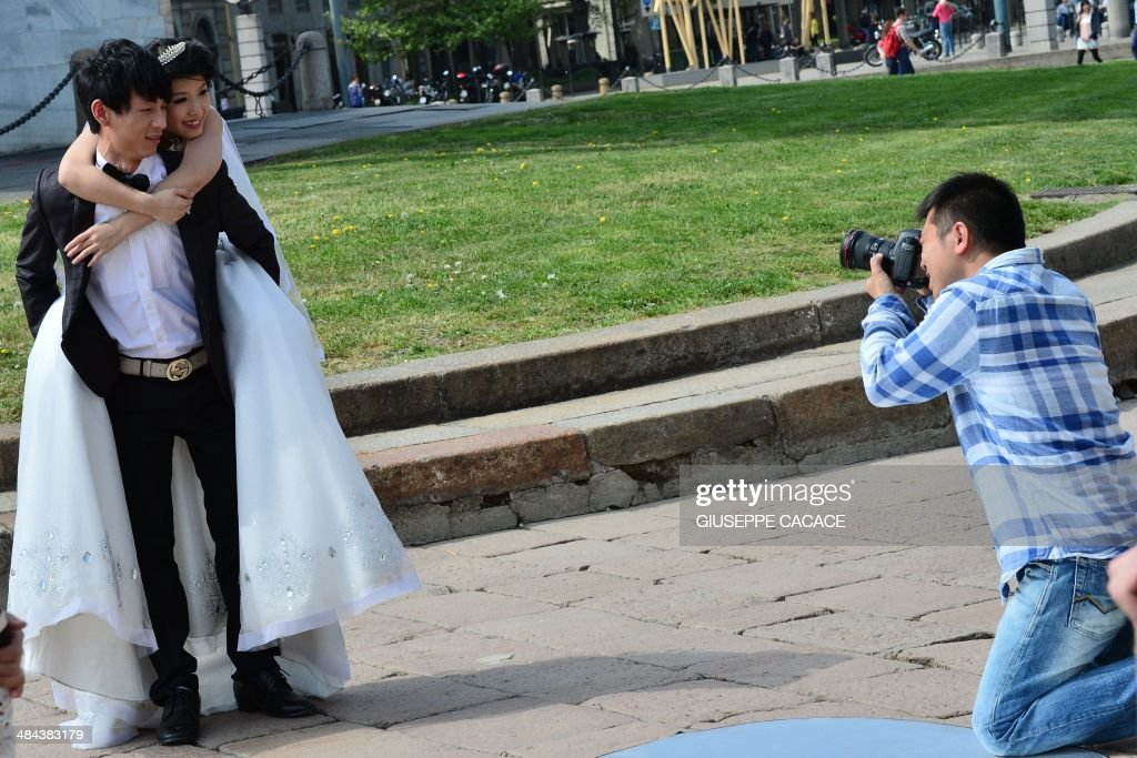 A 'just married' couple poses for a photograph near the Arco della Pace on April 12, 2014 in Milan.