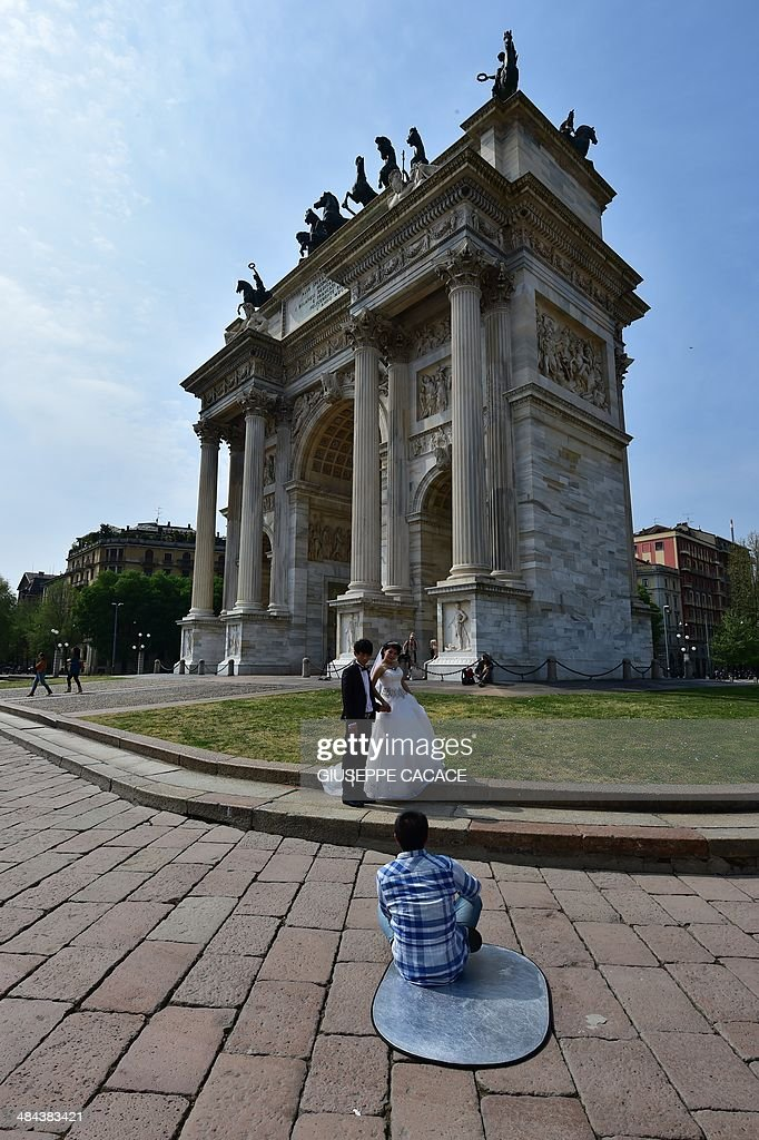 A 'just married' couple poses for a photograph near the Arco della Pace on April 12, 2014 in Milan. AFP PHOTO / GIUSEPPE CACACE