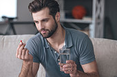 Handsome young man holding a glass of water and looking at a pill in his hand while sitting on the couch at home