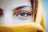 Young woman, with striking beautiful eye color wears a bright yellow , millenial yellow ochre scarf around her face and head, close up on only her eyes. Perhaps it is warm weather gear, could also be