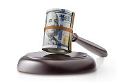 Judge gavel with roll of dollar banknotes on white background.