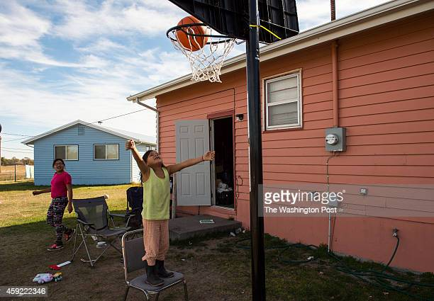 Justice Bull Shows looks on as Ariya Bull Shows makes the basket at her home on Rosebud Indian Reservation in South Dakota on Friday October 24 2014