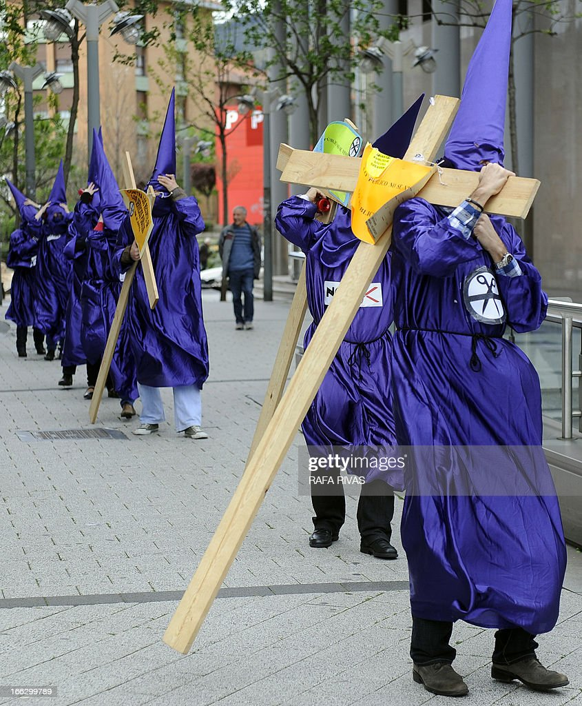 Justice civil servants of Baracaldo's court, wearing penitents costumes and carrying wooden crosses, take part in a protest against the government's spending cuts in justice services outside the court in the Northern Spanish Basque city of Baracaldo on April 11, 2013.