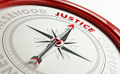Arrow of a compass is pointing justice text on the compass. Arrow, justice text and the frame of compass are red in color. Horizontal composition qith copy space. Justice concept.
