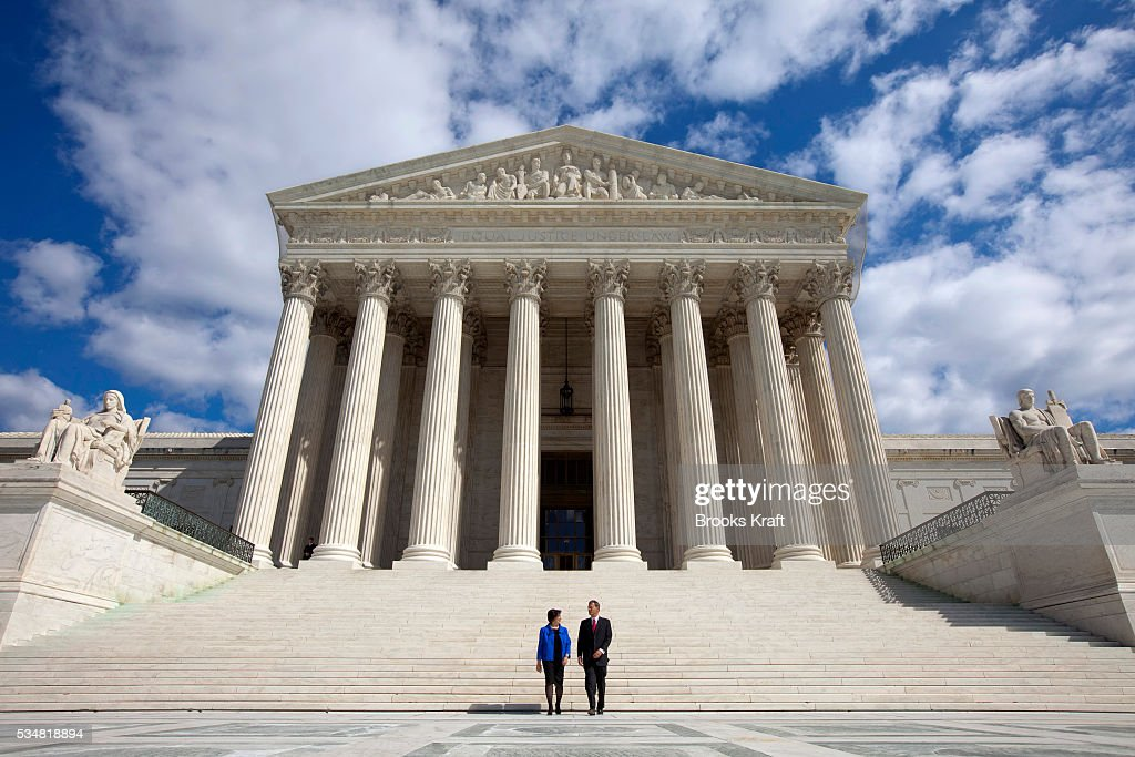 Justice Elena Kagan walks down the steps of the Supreme Court with Chief Justice of the United States John Roberts following her formal investiture...