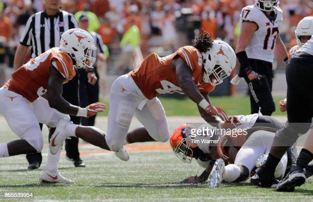 Justice Hill of the Oklahoma State Cowboys is tackled by Malik Jefferson of the Texas Longhorns and Kris Boyd in the second half at Darrell K...