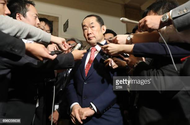 Justice Minister Katsutoshi Kaneda is surrounded by journalists after upper house of parliament passed the controversial antiterror law in Tokyo on...
