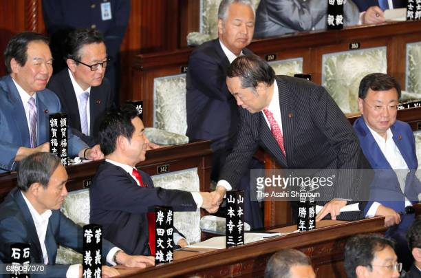 Justice Minister Katsutoshi Kaneda shakes hands with Regional Revitalization Minister Kozo Yamamoto after the ruling coalition of the Liberal...