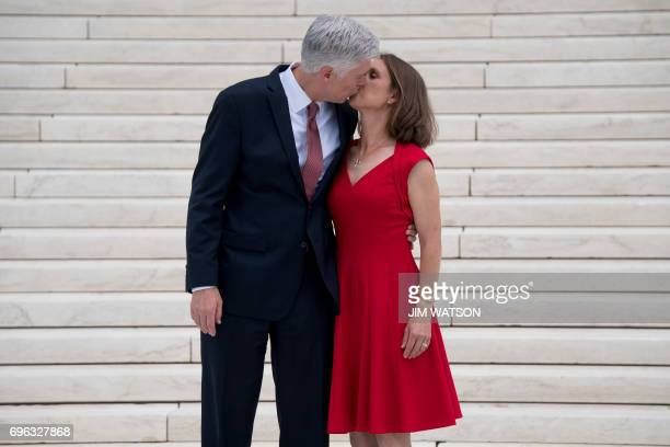 Justice Neil Gorsuch kisses his wife Marie Louise Gorsuch on the steps of the US Supreme Court in Washington DC June 15 2017 / AFP PHOTO / JIM WATSON