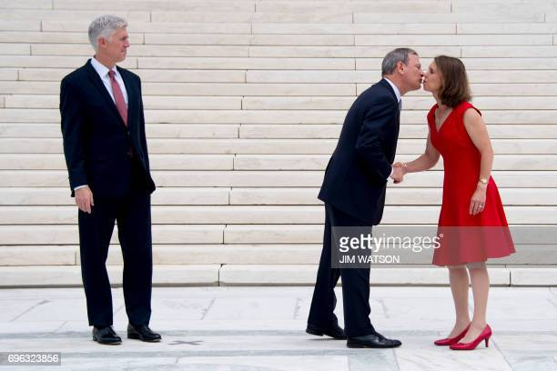 Justice Neil Gorsuch looks on as Chief Justice John Roberts kisses Marie Louise Gorsuch on the steps of the US Supreme Court in Washington DC June 15...