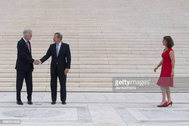 Justice Neil Gorsuch shakes hands with Chief Justice John Roberts as his wife Marie Louise Gorsuch arrives on the steps of the US Supreme Court in...